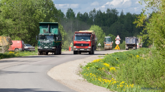 Гружённый доверху самосвал проезжает мимо места гарантийного ремонта дороги.