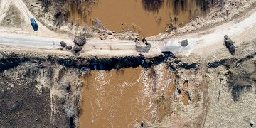 В ночь на 9 апреля уровень воды в реке Каменка поднялся до рекордных отметок. Дорогу начало подмывать. Школьный автобус не смог проехать за школьниками и воспитанниками детского сада.  <p>Днём дорожные службы восстановили проезд, но его вновь размыло потоком воды.  <p>Как сообщили в региональном правительстве со ссылкой на «Новгородавтодор» на месте размыва дорога закрыта на 30 дней.  <p>Уровень воды спал и уже спустя два дня местные жители на легковых автомобилях ездят по закрытой дороге.